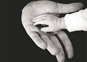 The hand of an infant reaches out to hold the hand of an older person.